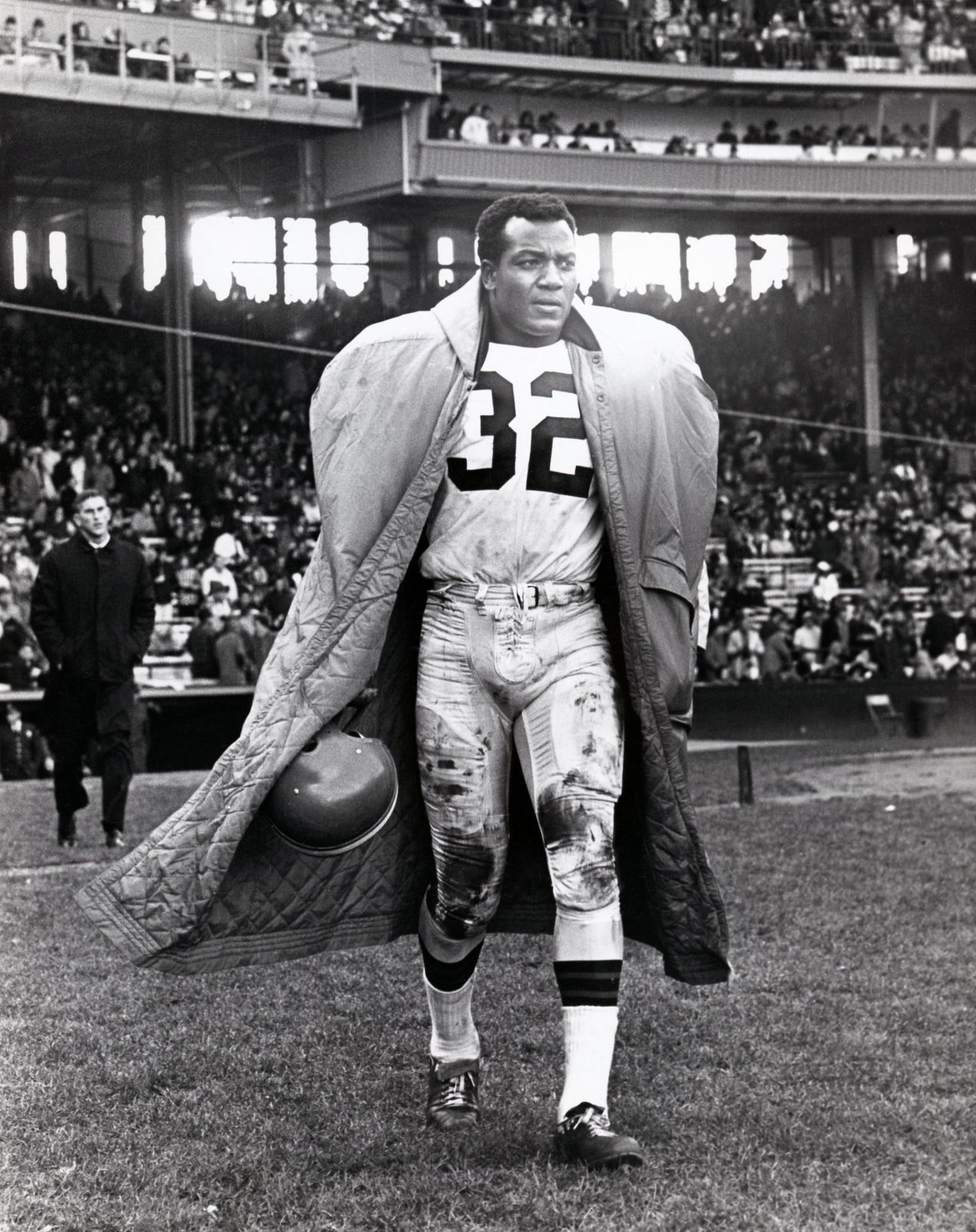Cleveland Browns fullback Jim Brown (32) tries to stay warm as he looks on from the sideline in Cleveland Stadium circa 1963.