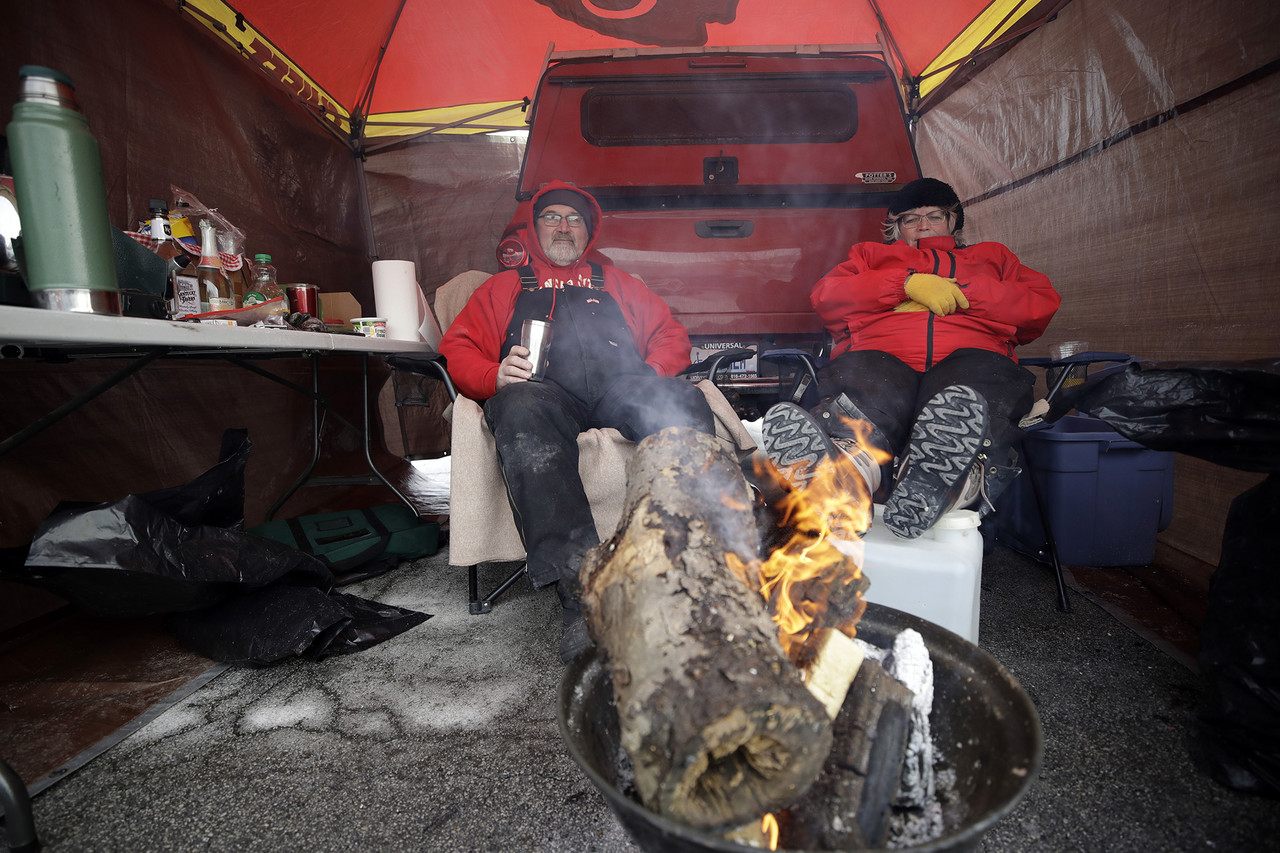 Phil and Lenee Meyer sit by the fire as they tailgate before the AFC Championship NFL football game between the Kansas City Chiefs and the New England Patriots, Sunday, Jan. 20, 2019, in Kansas City, Mo. (AP Photo/Elise Amendola)