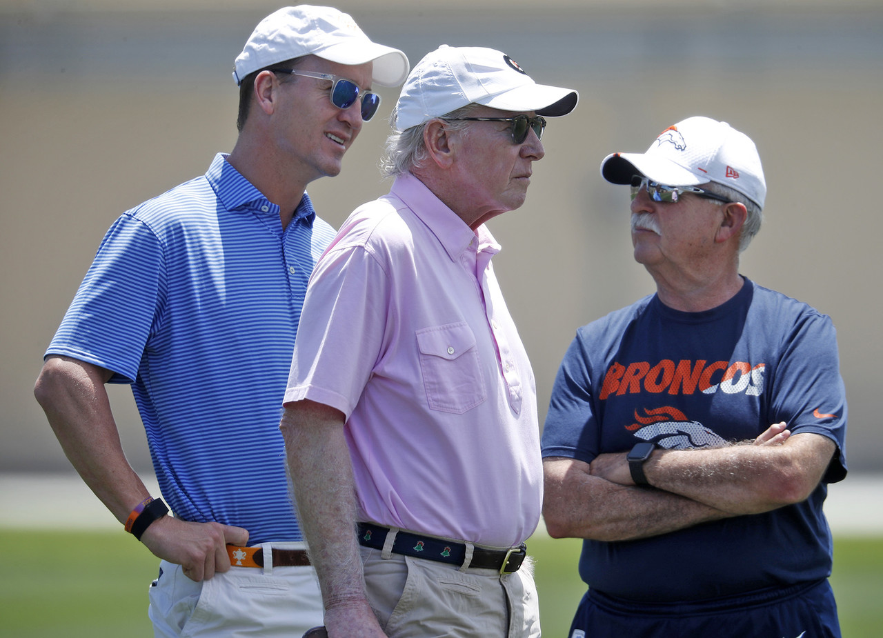Former NFL quarterbacks Peyton Manning, left, and father Archie, center, chat with Denver Broncos head trainer Steve Antonopulos as the Broncos work out at the team's NFL football training facility Wednesday, June 5, 2019, in Englewood, Colo.