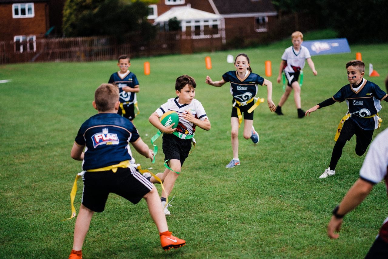 A child runs the ball during the NFL Flag Regional Tournament on Thursday, June 20, 2019 in Tewkesbury.