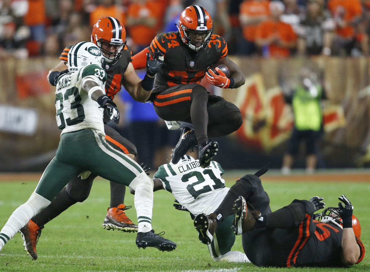 Cleveland Browns running back Carlos Hyde (34) jumps over defenders during the second half of an NFL football game against the New York Jets, Thursday, Sept. 20, 2018, in Cleveland.
