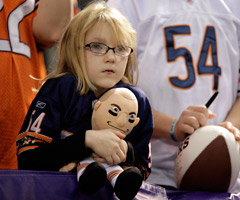 A young Chicago Bears fan holds a Brian Urlacher doll. (Charlie Neibergall/Associated Press)