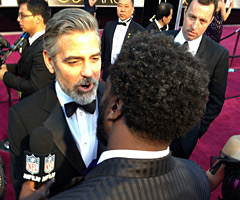 George Clooney (left) and Ed Reed chat before the Oscars on Sunday.