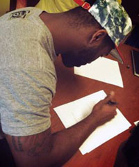 Darrelle Revis signs his six-year, $96 million contract with the Tampa Bay Buccaneers on Sunday. (John Geiger/Twitter)