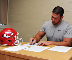Eric Fisher signs his Kansas City Chiefs contract (courtesy @kcchiefs)