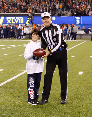NFL Play 60 Super Kid Thomas Brown hands the game ball before Super Bowl XLVIII at Metlife Stadium.