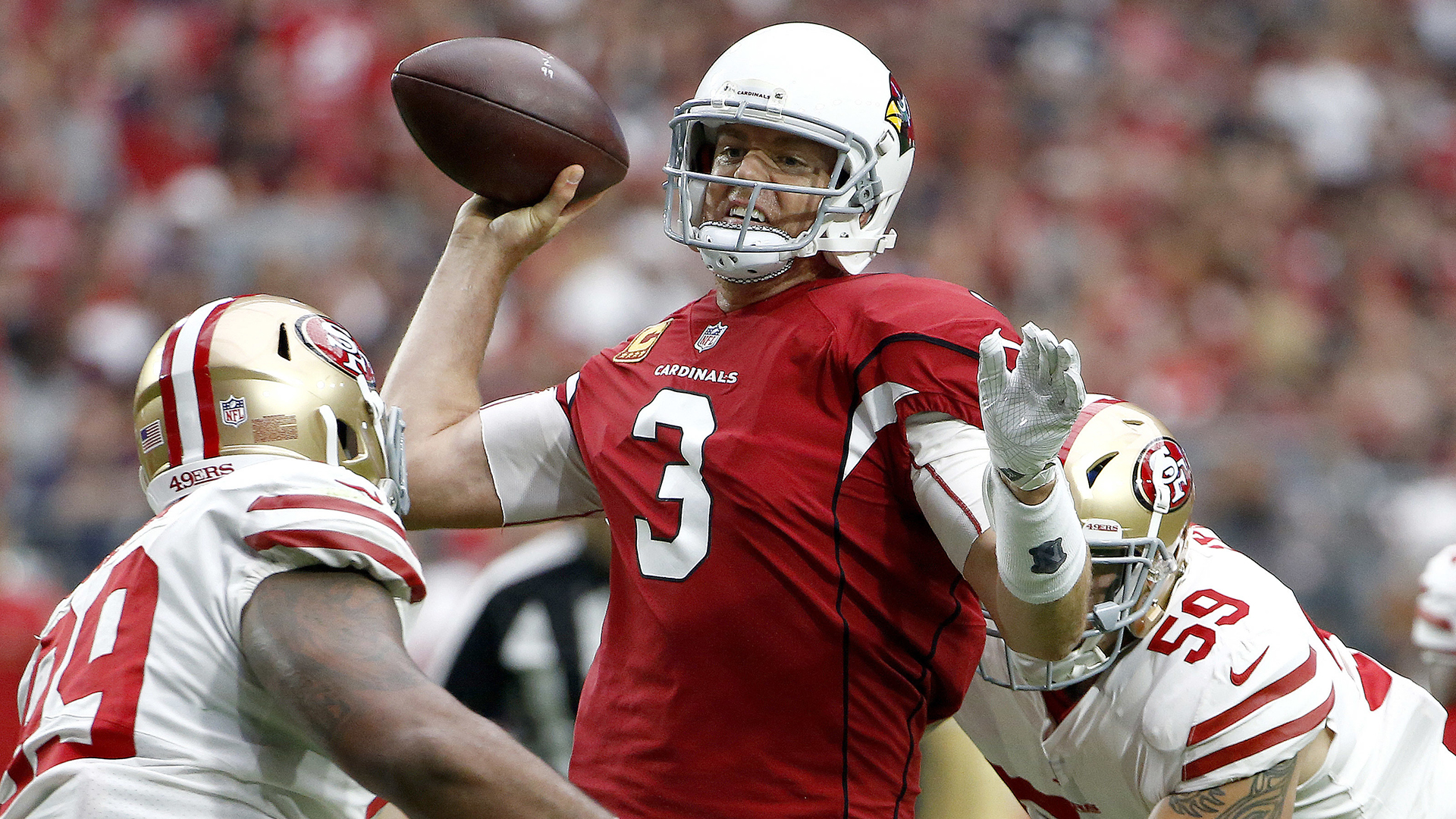 Arizona Cardinals quarterback Carson Palmer (3) is hit as he throws by San Francisco 49ers defensive end Aaron Lynch (59) to force an interception during the first half of an NFL football game, Sunday, Oct. 1, 2017, in Glendale, Ariz.