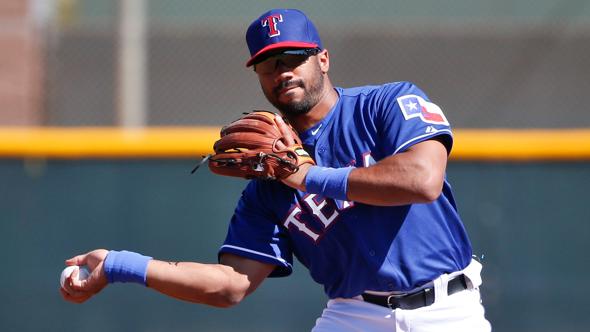 Seattle Seahawks quarterback Russell Wilson makes a pivot at second base as he rehearses his throw during infield practice prior to a Rangers spring training baseball game against the San Diego Padres Saturday, March 28, 2015, in Surprise, Ariz.  (AP Photo/Lenny Ignelzi)