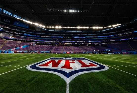 Large NFL logo shown on the fifty yard line in an empty stadium