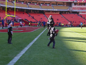Raiders players play a game of catch with young fans