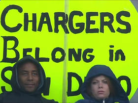 Chargers fans hold up signs with hopes of keeping the team in San Diego